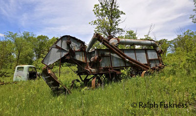 60046698 - an old threshing machine and truck are left in a grassy meadow.